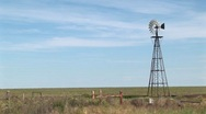 Long shot of a windmill turning in a ranch pasture Stock Footage