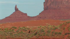Cowboys riding through Monument Valley Tribal Park in Arizona Stock Footage