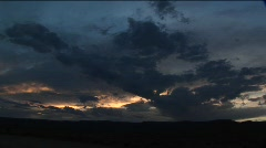 Storm clouds cluster in the sky over a desert Stock Footage