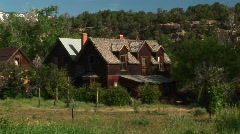 Medium shot of an abandoned ranch house sitting in a grove of trees Stock Footage