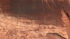 Pan up shot of ancient petroglyphs on a sandstone cliff Stock Footage