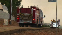 Medium shot of fire trucks racing down a street toward a wildfire Stock Footage