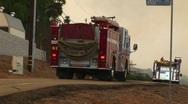 Stock Video Footage of Medium shot of fire trucks racing down a street toward a wildfire