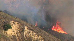 Wildfires burning on a smoky hillside in southern California Stock Footage