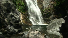 A waterfall flowing into a reflecting pool in Big Sur, California Stock Footage