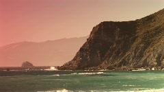 Long-shot of waves splashing up along a steep California coastline Stock Footage