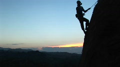 Rock climber silhouetted against a golden-hour-sky Stock Footage