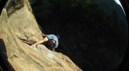 Fish-eye shot of a rock climber climbing up cliff face Stock Footage