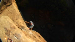 Aerial-shot of a rock climber climbing up a cliff face Stock Footage