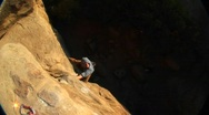 Stock Video Footage of Aerial-shot of a rock climber climbing up a cliff face