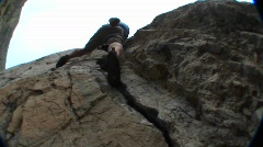 Pan-up past a rock climber scaling a cliff face Stock Footage