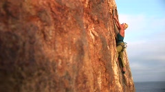 Rock climber attempting to climb a cliff wall over the Pacific Ocean Stock Footage