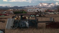 Medium shot of rusting cars in front of the Rocky Mountains Stock Footage