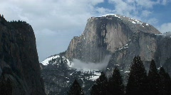 Yosemite's Half Dome hosting clouds and winter snow Stock Footage