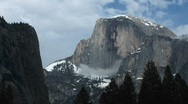 Stock Video Footage of Yosemite's Half Dome hosting clouds and winter snow