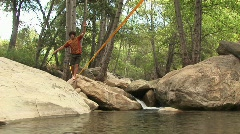 Medium-shot of a young man slacklining across a swimming hole Stock Footage