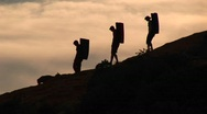 Back-packers and a dog silhouetted against an evening sky Stock Footage