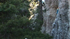 Medium-shot of a climber making her way up a granite cliff face Stock Footage