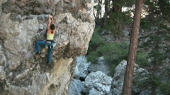 Medium-shot of a rock climber making her way up a sheer granite cliff face Stock Footage