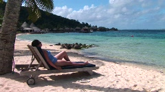 A woman relaxes on a beach chair on a tropical beach Stock Footage