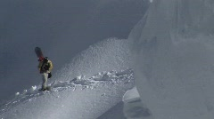 Hikers with snowboards climb a snowy mountain. Stock Footage