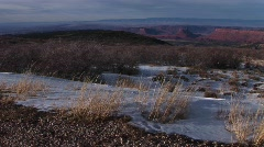The desert southwest with distant buttes and snow in the foreground - stock footage