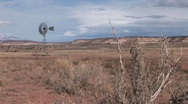 Long shot of an old windmill standing out in a desert plain Stock Footage
