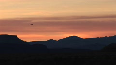 Long shot of a helicopter flying over low hills at golden-hour Stock Footage
