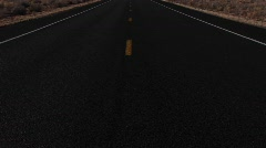 Pan-up slowly to an empty highway stretching through the desert Stock Footage