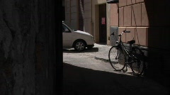 A shadow frames a bicycle and car near a rock building Palermo, Stock Footage