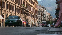 Old buildings line a busy street with vehicles and pedestrians - stock footage