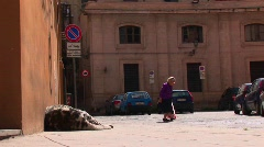 An old woman walks pass a large body mass lying against a building Stock Footage