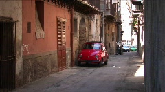 Cars parked along stone buildings in a tightly spaced alley Stock Footage