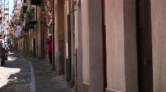 An alley between closely placed houses with clothes drying from - stock footage