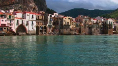 Ocean water near beach houses in Cefalu, Italy. Stock Footage