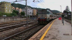 A train passes through a train yard and town in Sicily, Italy. Stock Footage