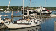 Sailboats and a sailing ship tied to docks in Maine. Stock Footage