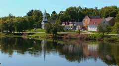 A lake reflects a peaceful New England town. Stock Footage