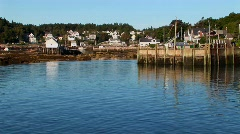 A boat passes a pier and lobster village in Stonington, Maine. Stock Footage