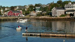 A small boat picks up a man from a dock near a lobster village Stock Footage
