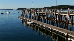 A boat leaves in the distance of a wooden dock near a lobster Stock Footage