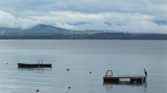 Clouds cover a mountain range in the distance of diving platforms Stock Footage