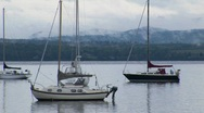 Stock Video Footage of Clouds cover a mountain range in the distance of sailboats on