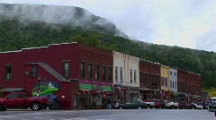 Vehicles drive downtown and pass old brick stores in Vermont. Stock Footage
