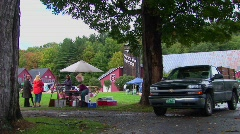Families picnic near trees and red barns at a Country Fair in Stock Footage