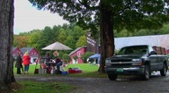 Stock Video Footage of Families picnic near trees and red barns at a Country Fair in