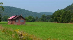 A cabin in the middle of a green field near the Allegheny Mountains Stock Footage