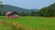 Stock Video Footage of A cabin in the middle of a green field near the Allegheny Mountains