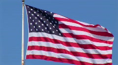 An American flag flies in the wind at day. Stock Footage