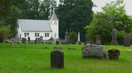 Gravestones stand in an old New England graveyard near a white church Stock Footage